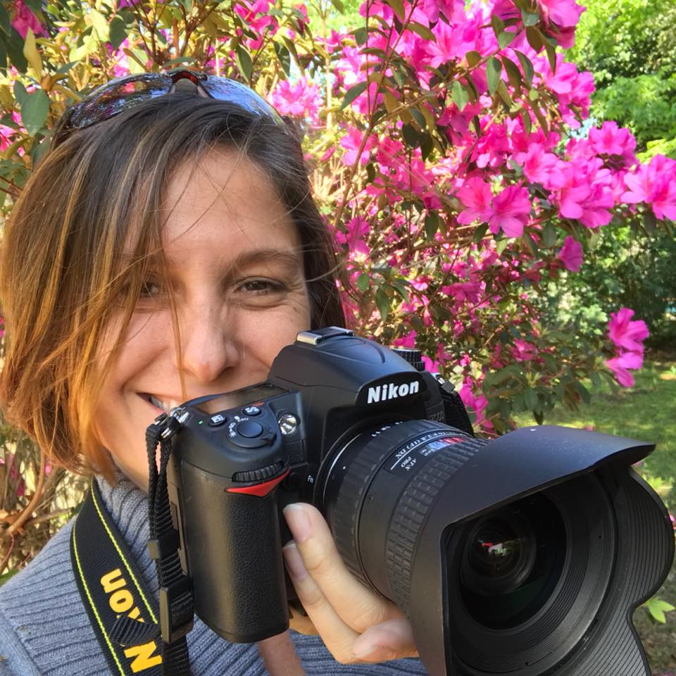 Kathleen Seide holding camera in front of flowers
